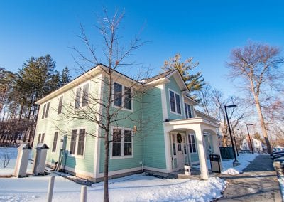 Exterior snapshot of the Youth and Family Services building that houses PUCK in the town of Bennington, Vermont. Photo description: A large mint green building illuminated by sunshine. The building has off-white trim. Snow is on the ground outside the two-story building and the trees are bare.