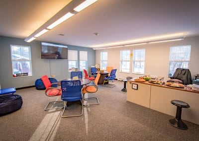 United Counseling Services in Bennington, Vermont. Photo description: A wide angle photo of PUCK's central space, well-lit by windows, showing tables with various therapeutic tools on them, colorful chairs, beanbags, bookcases full of books, a flat screen TV mounted on the wall, and other various items.