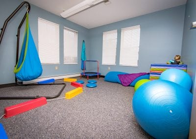 The sensory therapy room at PUCK. It is filled with a variety of therapeutic tools for helping children, especially those with sensory processing disorders. Photo description: A bright, colorful space filled with a swing, a trampoline, bouncy balls, a body stocking, and other toy-like items.