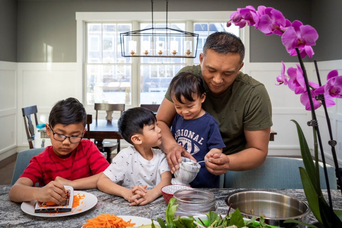 Pictured above / image description: A family prepares the ingredients for a healthy meal together. The young child on the left is shredding carrots, and a parent is supervising their two other children. In the forefront are salad greens and other ingredients in bowls and plates.
