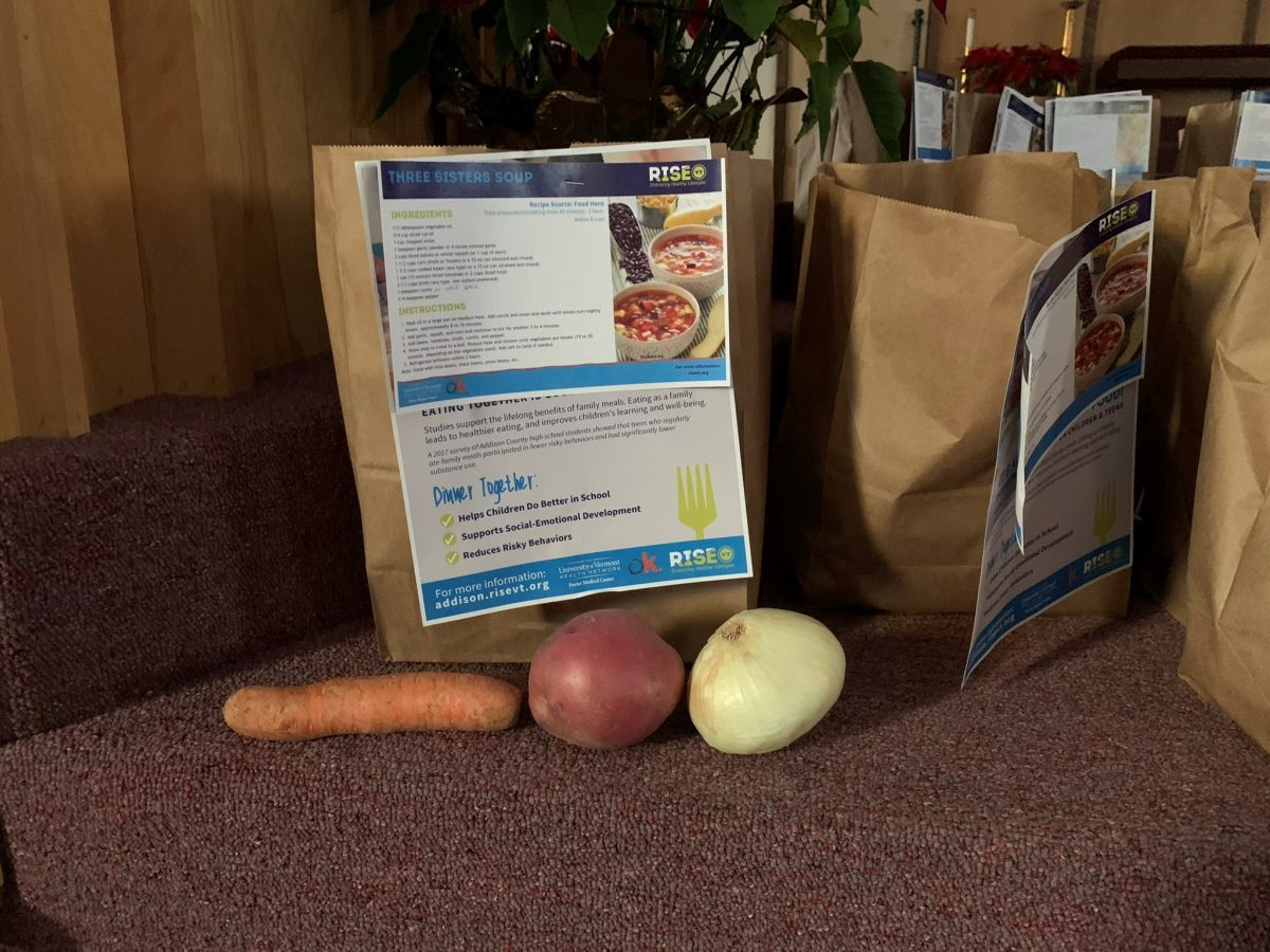 A photograph of a Rise Vermont Meal Kit - food in a bag and a Rise Vermont recipe card is attached to the bag.