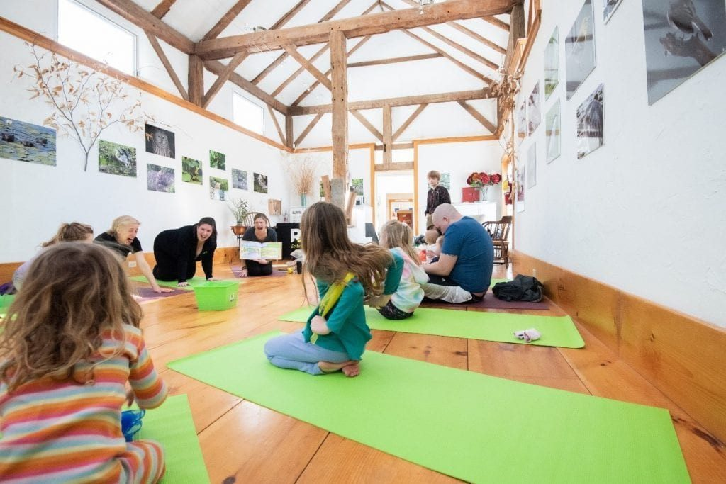 Children sit on green yoga mats with their parents and program manager, Elisha Underwood, in an open room.