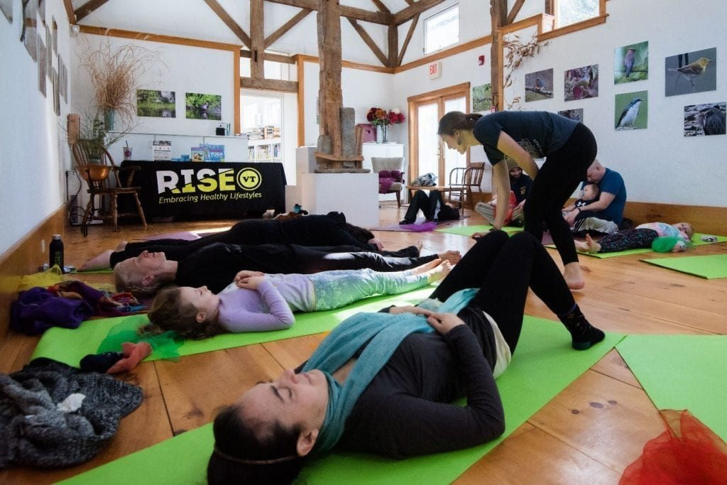 Children and parents lay on green yoga mats while the yoga teacher walks around giving suggestions for improving their poses. In the background there is a table with a RiseVT tablecloth in a large room.