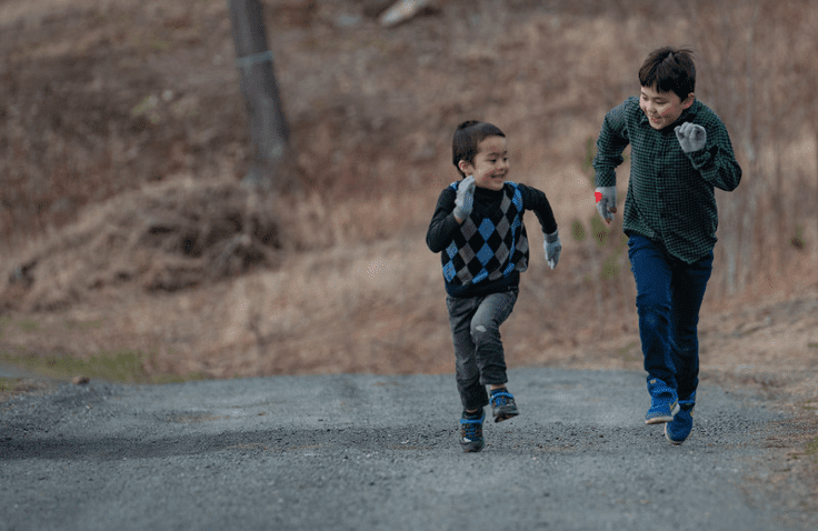 Two brothers are running up a dirt road together in the fall. The one is smaller than the other. They are both smiling as they race each other.