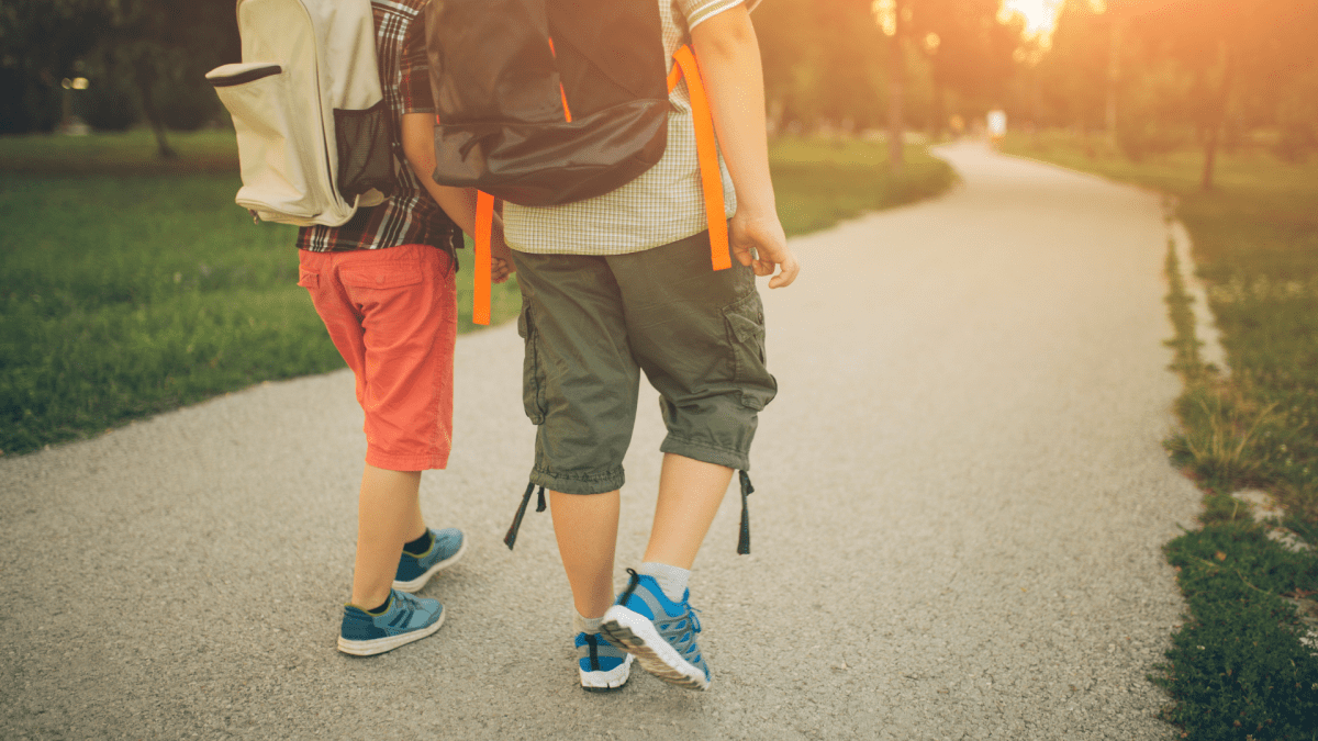 Walkability: Two school aged siblings walking home from school. They are both wearing backpacks and sneakers walking along a sidewalk. The sun is lower in the sky.