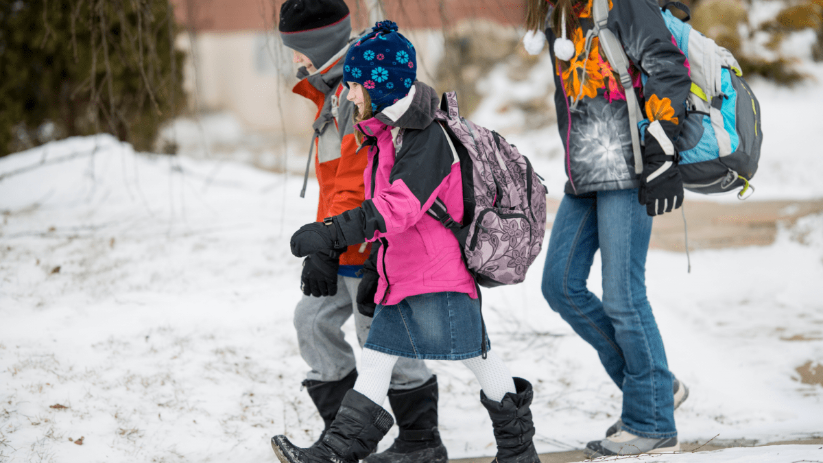 Three children walk to school along the sidewalk. It is winter and there is snow on the ground. They are all wearing backpacks and coats.