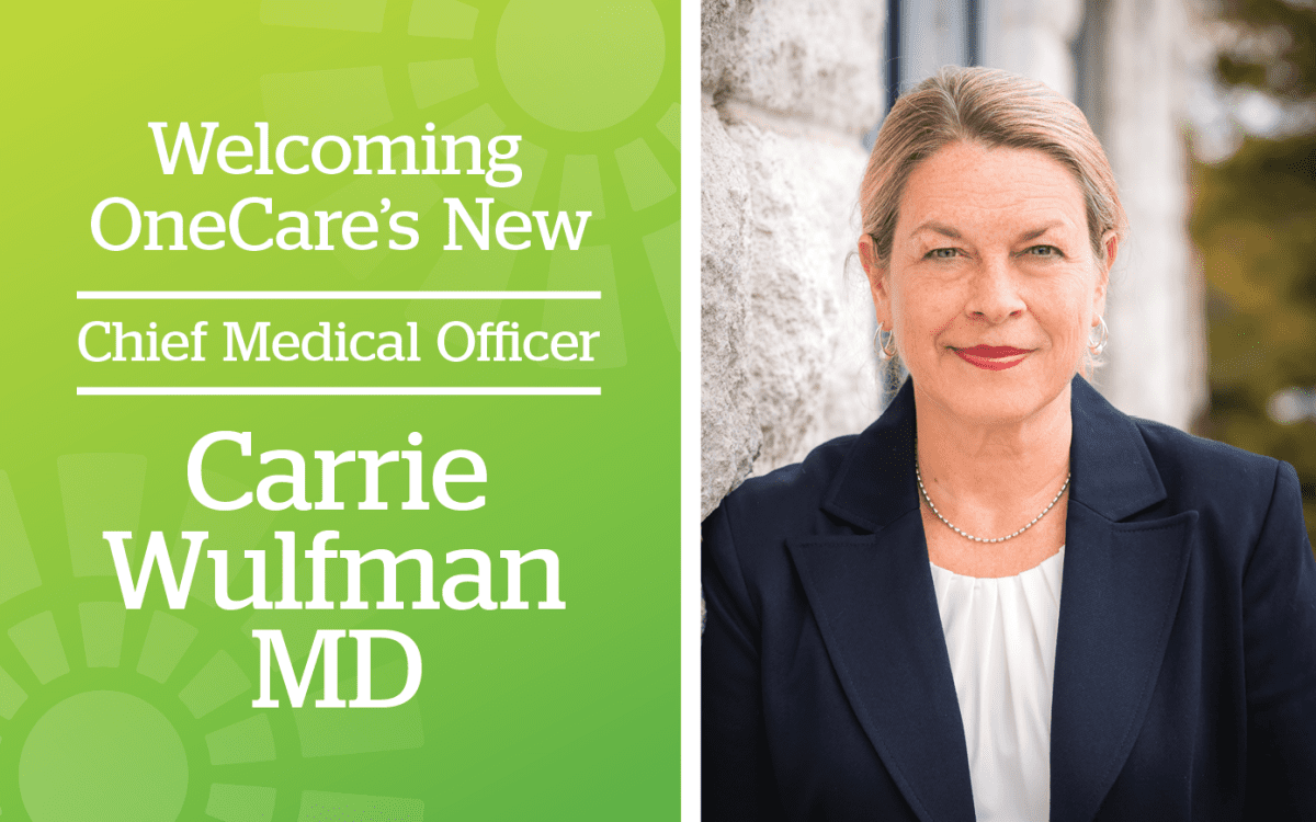 Cover Image - Welcoming OneCare New Chief Medical Officer Carrie Wulfman, MD. Right side is photo of smiling woman in dark navy blue blazer and white shirt.