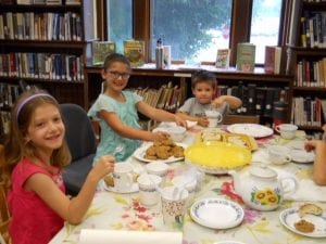 Three young Haston Library patrons sitting down to tea and oatmeal cookies in the Children's Room.